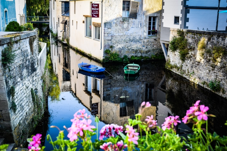 Blue and green boats floating on l'Aure in the middle of the old town in Bayeux